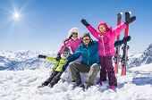 Laughing family in winter vacation with ski sport on snowy mountains. Happy man and woman with sons  poster