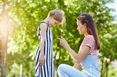 Strict mother talking to her naughty daughter in park poster
