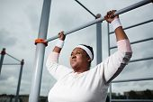 Persistant chubby girl trying to do difficult exercise while hanging on bar of outdoor sport facilit poster
