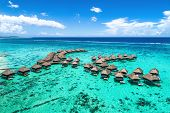 Beach travel vacation Tahiti hotel overwater bungalows luxury resort in coral reef lagoon ocean. Moo poster