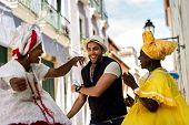 Tourist dancing with local Baianas in Salvador, Bahia, Brazil poster