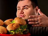 Fat man eating fast food hamberger and carries treat for friends on tray. Hamburgers close-up. Perso poster