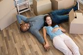 Happy multiethnic couple lying on floor after moving house. Top view of woman lying on stomach of bl poster
