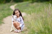 Little girl plays and hgs goatling in country, spring or summer nature outdoor. Cute kid with baby a poster