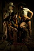 stock photo of threesome  - Young cowboy with pair cowboy girls against wooden background - JPG