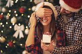 Young couple have Christmas surprise for holiday poster