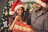 Cheerful man and woman opens Christmas gift  poster