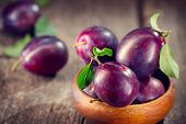 Plum. Healthy juicy ripe organic plums fruit close-up, on wooden table. Prune. Sweet fruit dessert poster