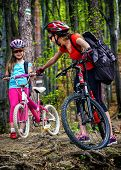 Bikes cycling family. Happy mother and daughter wearing helmet are cycling on bicycles into forest.  poster