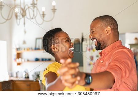 poster of Cute mature couple dancing at home for their anniversary. Happy black woman enjoying a dance in the