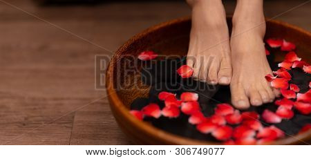 poster of Closeup Shot Of A Woman Feet Dipped In Water With Petals In A Wooden Bowl
