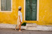 Young Beauty Tourist Woman Goes Along Street In An Old Greek Town. Greece. Sightseeing In Kefalonia. poster