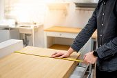 Asian Man Interior Designer Using Tape Measure For Measuring Size Of Wooden Countertop In Modern Kit poster