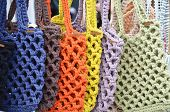 Hand-tied Multi-colored Bags On The Storefront.eco Friendly Reusable Bags . Zero Waste Shopping Conc poster