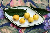 foto of loquat  - A small tray with five loquats and leaves on a table - JPG