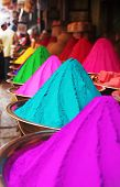 stock photo of haldi  - Colorful piles of finely powdered dyes used for hindu religious activities like holi on display in an indian shop at mysore market - JPG