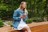 Image of a happy young pretty blonde woman outdoors in park using mobile phone. poster