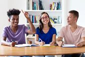 African American Student Raising Hand In Classroom Of School With Nerdy Female Student And Caucasian poster