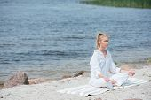 Peaceful Blonde Woman With Closed Eyes Practicing Yoga Near River poster