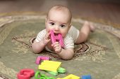 picture of love bite  - The baby boy biting a alphabet on a carpet at home - JPG
