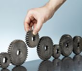 stock photo of tooth gap  - Man adding a cog gear in a row of old cog gears - JPG