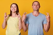 Portrait Of Cheerful Energetic Couple Standing Close To Each Other, Crossing Their Fingers, Raising  poster