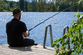 Mature Man Fishing From Wooden Pier Near Cottage On Lake In Finland At Summer poster