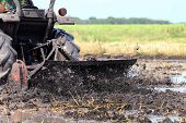 Tractor Moves Through A Wet Puddle Mud Black, Tractor Ploughing At Rice Field And Splash Of Muddy We poster