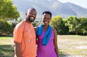 Portrait of black sporty couple looking at camera at park with copy space. Happy mature man and smil poster