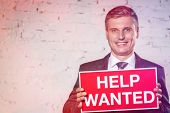 Portrait of smiling businessman holding help wanted sign while standing against white brick wall poster