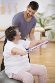 Elderly Pensioner Exercising With Resistance Bands With Her Professional Physiotherapist poster