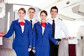 picture of cabin crew  - Friendly cabin crew in an airplane smiling - JPG