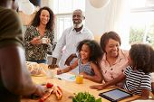 Grandparents Sitting At Table With Grandchildren Playing Games As Family Prepares Meal poster