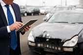 Male Insurance Loss Adjuster With Digital Tablet Inspecting Damage To Car From Motor Accident poster