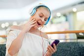 Portrait Of A Happy Girl Listening Music On Line With Wireless Headphones From A Smartphone. Happy T poster