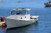 picture of lobster boat  - A lobster boat is docked in a harbor - JPG