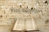stock photo of torah  - Excerpt from a Torah scroll the background kotel sacred to the Jewish people - JPG