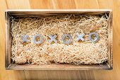 stock photo of xoxo  - Hugs and kisses symbols xoxo in a wooden gift box filled with natural raffia - JPG