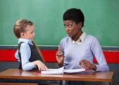 Young African American female teacher scolding schoolgirl at desk in classroom