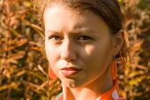 stock photo of pouty lips  - girl sunlit with pouty lips and orange earrings - JPG
