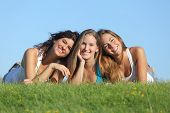 stock photo of three life  - Portrait of a group of three happy teenager girls smiling lying on the grass with the sky in the background - JPG