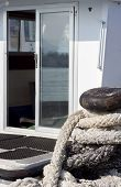 image of bollard  - Old rope on bollard forward white boat with an open glass door moored dock - JPG