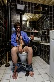 Drunk Man Sits In A Toilet With Whiskey
