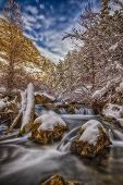 stock photo of cottonwood  - The Big cottonwood Canyon River in Big Cottonwood Canyon in the Wasatch national forest in Utah after a snow storm has moved through slow exposure on the river and partly cloudy sky