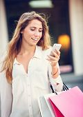 Attractive young woman shopping at the mall using cell phone