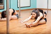 image of pole dance  - Group of Hispanic women stretching and warming up for their pole dancing class