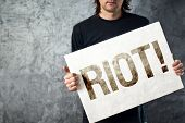 Riot. Man Holding Poster With Printed Protest Message