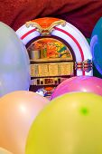 stock photo of jukebox  - Background of a group of colorful baloons and a jukebox - JPG