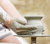image of molding clay  - child learning how to make a pot on a pottery wheel - JPG