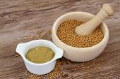 stock photo of mustard seeds  - Mustard seeds in wooden mortar and mustard in white bowl with copy space - JPG